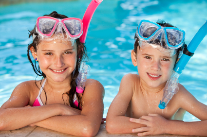 Boy and Girl In Swimming Pool with Goggles and Snorkel